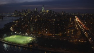 AX65_0281 - 5K stock footage aerial video flyby public housing, and FDR Drive on Lower East Side, with Lower Manhattan skyline in the background, NYC, winter, night