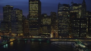 AX65_0284 - 5K stock footage aerial video of riverfront skyscrapers and the Staten Island Ferry Terminal in Lower Manhattan, New York City, winter, night