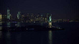 AX65_0285 - 5K stock footage aerial video of Statue of Liberty and the skyline of Lower Manhattan, New York City, winter, night