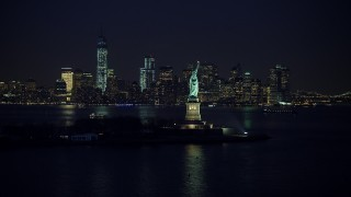 AX65_0286 - 5K stock footage aerial video of Statue of Liberty, and the skyline of Lower Manhattan in the background, New York City, winter, night
