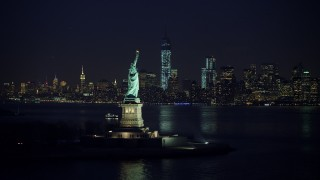 AX65_0287 - 5K stock footage aerial video of Statue of Liberty, and the skyline of Lower Manhattan and Freedom Tower in the background, New York City, winter, night