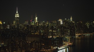 AX65_0303 - 5K stock footage aerial video of riverfront power plant, Empire State Building, and Midtown Manhattan skyline, New York City, winter, night