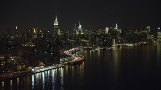 AX65_0304 - 5K stock footage aerial video flyby a riverfront power plant, Empire State Building, and the Midtown Manhattan skyline, New York City, winter, night
