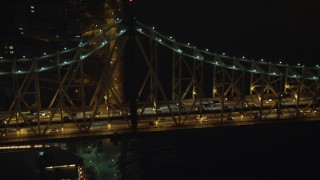 AX65_0314 - 5K stock footage aerial video track slow traffic crossing the Queensboro Bridge, New York City, winter, night