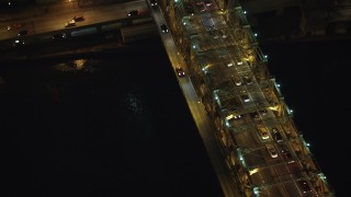 AX65_0315 - 5K stock footage aerial video of a bird's eye view of slow traffic crossing the Queensboro Bridge, New York City, winter, night