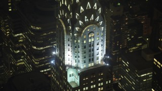 AX65_0317 - Aerial stock footage of Orbit the upper floors of the Chrysler Building in Midtown Manhattan, New York City, winter, night