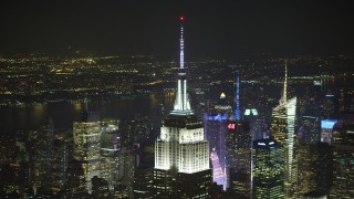 AX65_0324 - 5K stock footage aerial video orbit the Empire State Building, Midtown Manhattan skyscrapers in background, New York City, winter, night