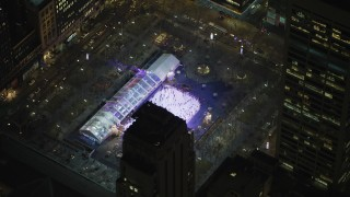 AX65_0330 - 5K stock footage aerial video orbit of the ice skating rink at Bryant Park, Midtown Manhattan, New York City, winter, night