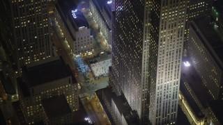 AX65_0332 - 5K stock footage aerial video orbit Rockefeller Center to reveal the ice skating rink, Midtown Manhattan, New York City, winter, night