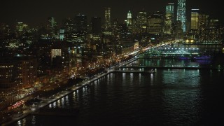 AX65_0373 - Aerial stock footage of Approach West Street and piers in Greenwich Village, skyscrapers in Lower Manhattan, New York City, winter, night