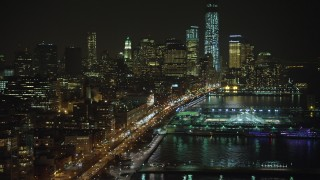 AX65_0374 - Aerial stock footage of Fly over Pier 40 and West Street to approach skyscrapers in Lower Manhattan, New York City, winter, night