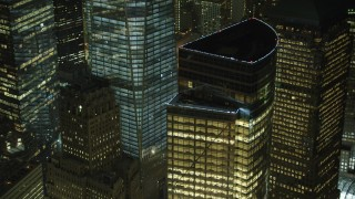 AX65_0380 - 5K stock footage aerial video flyby World Trade Center skyscrapers to reveal glimpses of the World Trade Center Memorial in Lower Manhattan, New York City, winter, night