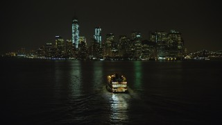 AX65_0387 - 5K stock footage aerial video flyby Staten Island Ferry sailing toward Lower Manhattan skyline, New York City, winter, night