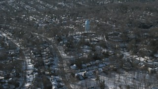 AX66_0029 - 5K stock footage aerial video of a water tower in snow covered suburban neighborhood, Manhasset, New York