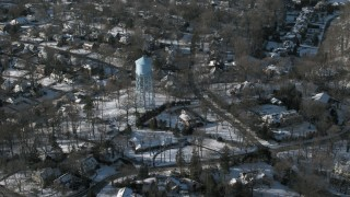 AX66_0030 - 5K stock footage aerial video of a water tower in snow covered neighborhood, Manhasset, New York