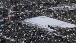 AX66_0033 - 5K stock footage aerial video of a residential neighborhood and sports field in snow, Great Neck, New York