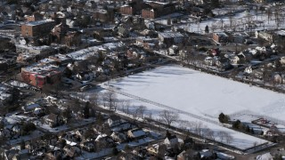AX66_0034 - 5K stock footage aerial video of suburban sports field in snow, Great Neck, New York