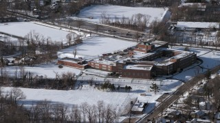 AX66_0035 - 5K stock footage aerial video of orbiting a school in snow, Great Neck, New York