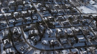 AX66_0036 - 5K stock footage aerial video of a bird's eye view of residential neighborhood in snow, Saddle Rock, New York