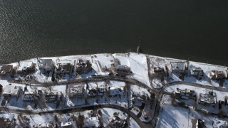AX66_0037 - 5K stock footage aerial video of a bird's eye view of waterfront homes in snow, Saddle Rock, New York