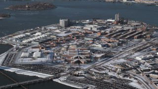 AX66_0049 - 5K stock footage aerial video of prison buildings on Rikers Island in snow, New York