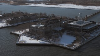 AX66_0125 - 5K stock footage aerial video of Ellis Island buildings with snow, New York