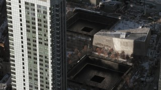 AX66_0139 - 5K stock footage aerial video tilt to World Trade Center Memorial with snow, New York City