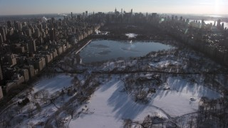 AX66_0198 - 5K stock footage aerial video of flying over Central Park in snow toward the lake, Manhattan, New York City