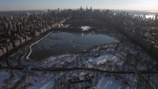 AX66_0199 - 5K stock footage aerial video approach lake in snowy Central Park, Manhattan, New York City