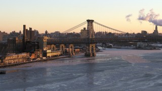 AX66_0229 - 5K stock footage aerial video of part of the Williamsburg Bridge on East River, New York City, sunset