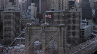 AX66_0235 - 5K stock footage aerial video orbit flag on top of the Brooklyn Bridge, New York City, at sunset