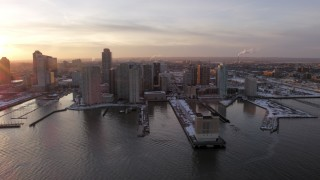 AX66_0245 - 5K stock footage aerial video of piers with snow and Downtown Jersey City, New Jersey skyscrapers, sunset