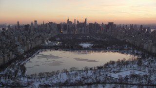 AX66_0297 - 5K stock footage aerial video of Central Park lake and Midtown Manhattan skyline in winter, New York City, twilight
