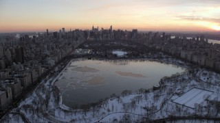 AX66_0298 - 5K stock footage aerial video fly over Central Park toward Midtown Manhattan skyline in winter, New York City, twilight