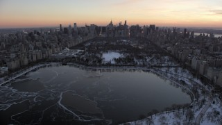 AX66_0299 - 5K stock footage aerial video flyby Central Park lake and Midtown skyline in winter, New York City, twilight