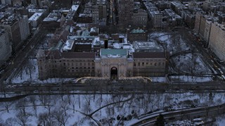 AX66_0303 - 5K stock footage aerial video approach Museum of Natural History in snow, New York City, twilight
