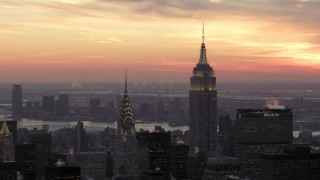 AX66_0313 - 5K stock footage aerial video orbiting Empire State Building and Chrysler Building in front of a beautiful winter sunset, New York City, twilight