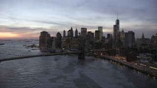 AX66_0365 - 5K stock footage aerial video of Brooklyn Bridge and Lower Manhattan skyscrapers in winter, New York City, twilight