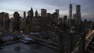 AX66_0367 - 5K stock footage aerial video fly over Brooklyn Bridge toward Lower Manhattan skyline in winter, New York City, twilight