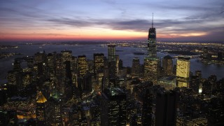 AX66_0391 - 5K stock footage aerial video of flying away from Lower Manhattan skyscrapers in winter, New York City, twilight