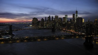 AX66_0399 - 5K stock footage aerial video of Manhattan and Brooklyn Bridges, approaching Lower Manhattan skyline, New York City, twilight