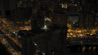 AX66_0403 - 5K stock footage aerial video of orbiting a flag on Brooklyn Bridge in winter, New York City, twilight
