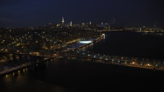 AX66_0410 - 5K stock footage aerial video of Williamsburg Bridge and Midtown Manhattan Skyline in winter, New York City, night