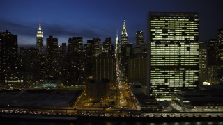 AX66_0418 - 5K stock footage aerial video of passing Midtown Manhattan skyscrapers and United Nations building, New York City, night