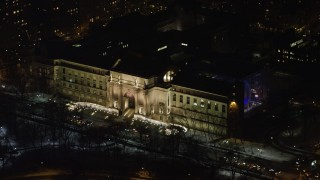 AX67_0016 - Aerial stock footage of 4K stock video aerial view of the front steps of the Museum of Natural History at night, Upper West Side, NYC, New York