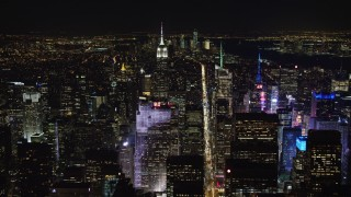 AX67_0018 - Aerial stock footage of 4K stock video aerial view fly over Rockefeller Center and follow 6th Street in Midtown Manhattan at night, New York City, New York