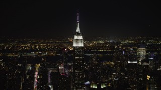AX67_0047 - Aerial stock footage of 4K stock video aerial view of orbiting the Empire State Building, Jersey City in the distance at night, Midtown Manhattan, New York City, New York