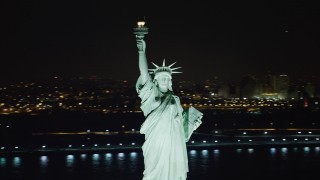 AX67_0072 - Aerial stock footage of 4K stock video aerial view of orbiting the famous Statue of Liberty at night, New York