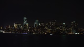 AX67_0075 - Aerial stock footage of 4K stock video aerial view of approaching Lower Manhattan skyline at night, New York
