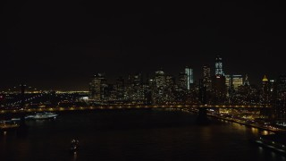 AX67_0080 - Aerial stock footage of 4K stock video aerial view fly over Manhattan Bridge to approach Brooklyn Bridge and Lower Manhattan skyline at night, New York